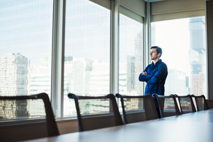A man standing with arms crossed in a meeting room looking out of a window at an urban landscape.の写真素材 [FYI02257412]