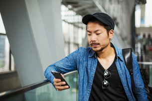 A man in a blue jacket in a modern building using his smart phone.の写真素材 [FYI02257428]
