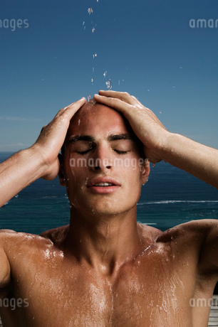 Nude man in front of an ocean, eyes closed and hands on head.の写真素材 [FYI02257433]