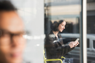 A seated woman seen through a window looking at a cellphone, with an out-of-focus man in the foregroの写真素材 [FYI02257437]