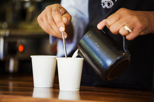 Close up of hot milk being poured from a jug into a paper cup.の写真素材 [FYI02257440]