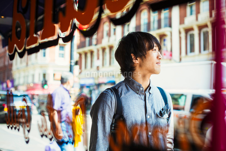 Young Japanese man enjoying a day out in London, walking past a shop window.の写真素材 [FYI02257441]
