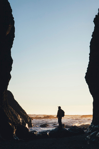 Silhouette of man standing between tall cliffs at dusk, the Pacific Ocean in the distance, Olympic Nの写真素材 [FYI02257452]