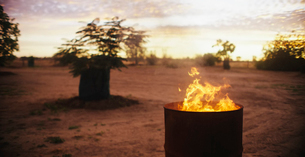 A fire burning in a barrel in an outback landscape.の写真素材 [FYI02257514]
