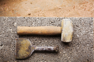 Close up of a hammer and chisel on a concrete slab.の写真素材 [FYI02257530]