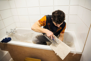 A builder, tiler sitting in a bathtub spreading adhesive on a tile.の写真素材 [FYI02257541]