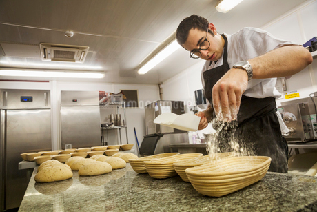 Baker sprinkling flower on bread dough and proving baskets in the kitchenの写真素材 [FYI02257567]