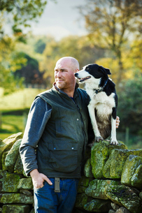 A sheep farmer, shepherd and his sheepdog standing beside him on a dry-stone wall.の写真素材 [FYI02257587]
