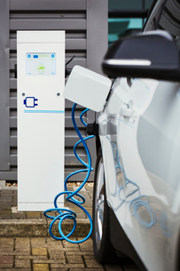 Electric car being charged with a cable connected to a wall socket.の写真素材 [FYI02257601]
