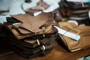 Close up of a stack of brown leather pieces in a shoemaker's workshop.の写真素材 [FYI02257606]