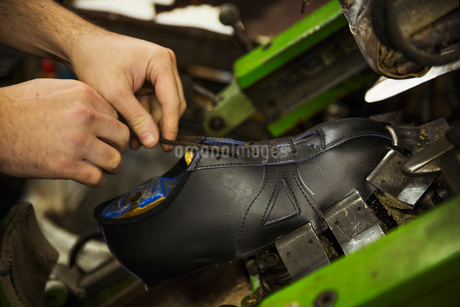 Close up of man standing in a shoemaker's workshop, tying the laces of a leather cycling shoe.の写真素材 [FYI02257635]