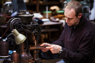 Man sitting at a large leather stitching machine in a shoemaker's workshop.の写真素材 [FYI02257664]