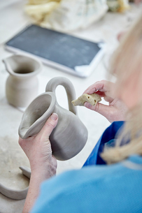 A woman using her hands to shape and smooth a wet clay jug to match another, making a pair.の写真素材 [FYI02257668]
