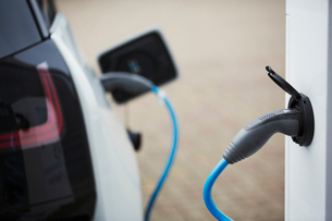 Electric car being charged with a cable connected to a wall socket.の写真素材 [FYI02257691]