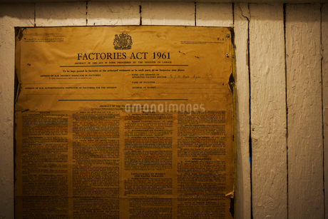 Yellowed poster of the Factories Act from 1961 on a wall in a shoemaker's workshop. Documentation.の写真素材 [FYI02257738]