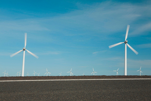 Wind turbines, tall white towers in the flat plains by a road near the Columbia River Gorge.の写真素材 [FYI02257753]
