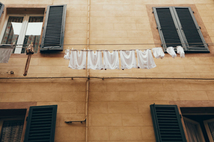 Laundry hanging from washing lines high above the street in Siena historic city in Tuscany,の写真素材 [FYI02257833]