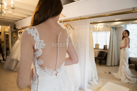 A young woman in a full length white wedding dress, looking at her reflection in the mirror in a briの写真素材 [FYI02257849]