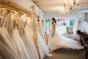 Rows of wedding dresses on display in a specialist wedding dress shop. A young woman trying on a wedの写真素材 [FYI02257874]