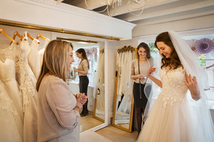 A bride trying on a dress, with the assistance of two women in a bridal boutique.の写真素材 [FYI02257886]