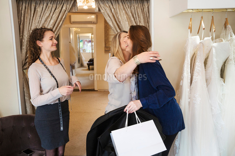 Three women in a wedding dress shop, one hugging and greeting a customer. A bridal boutique.の写真素材 [FYI02257901]