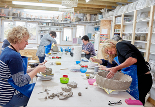 Five people, women in a pottery studio, working on handbuilding clay objects.の写真素材 [FYI02257935]