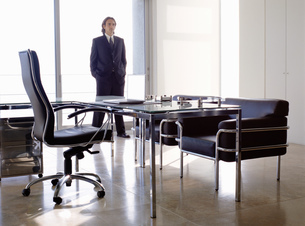Businessman wearing dark suit standing indoors in an office behind desk with chairs.の写真素材 [FYI02257942]