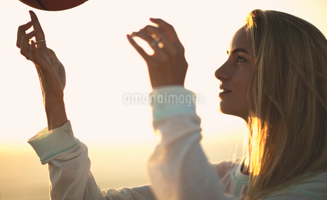 Young woman standing in front of a sunset spinning a basketball on her finger.の写真素材 [FYI02257943]