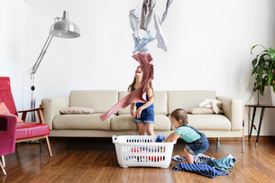 Young boy and girl standing in front of sofa, throwing laundry in air, laundry basket on hardwood flの写真素材 [FYI02257945]