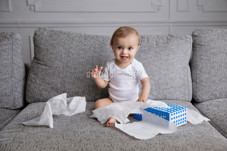 Baby boy with blond hair sitting on sofa, playing with tissue paper.の写真素材 [FYI02257949]