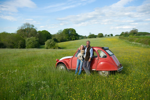 Man and woman standing side by side on a meadow, holding small dog, leaning against red vintage car.の写真素材 [FYI02257950]