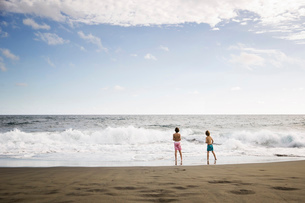 Two children, young boys playing at the water's edge on a sandy beach.の写真素材 [FYI02257960]
