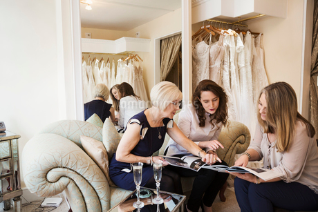 Three women in a wedding dress shop, one bride to be and two retail advisors looking through brochurの写真素材 [FYI02257969]