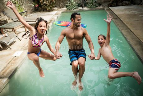 A man holding hands with two children jumping backwards into a swimming pool.の写真素材 [FYI02257981]