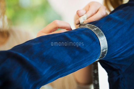 A sales assistant, dressmaker or seamstress, taking the measurements of a client in a wedding dressの写真素材 [FYI02257982]