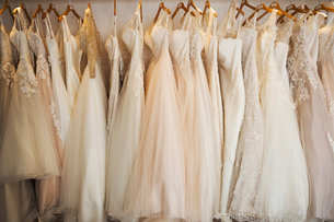 Rows of wedding dresses on display in a specialist wedding dress shop. A variety of colour tones andの写真素材 [FYI02257998]