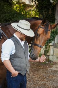 Bearded man wearing a stetson standing beside a brown horse.の写真素材 [FYI02257999]