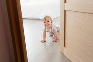 Baby boy wearing striped onesie crawling across hardwood floor towards open door.の写真素材 [FYI02258006]