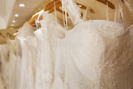 Rows of wedding dresses on display in a specialist wedding dress shop. A variety of colour tones andの写真素材 [FYI02258023]