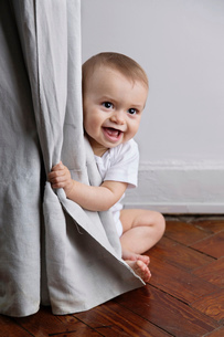 Baby boy with blond hair sitting on hardwood floor, peering from behind curtain.の写真素材 [FYI02258029]