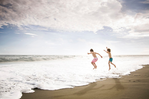 Two children, young boys playing at the water's edge on a sandy beach.の写真素材 [FYI02258055]