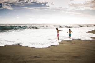 Two children, young boys playing at the water's edge on a sandy beach.の写真素材 [FYI02258076]