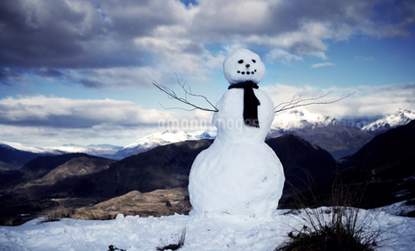 Snowman wearing a scarf, snow-capped mountains in the distance, cloudy sky.の写真素材 [FYI02258078]