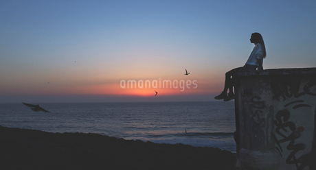 Side view of a young woman sitting on a wall with a sunset behind.の写真素材 [FYI02258080]