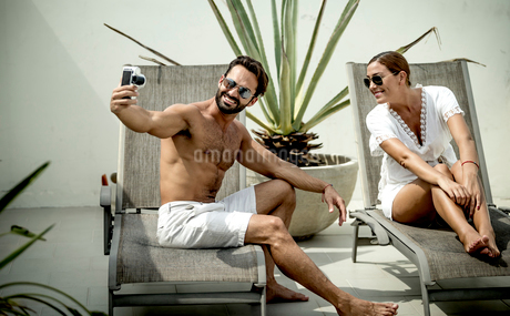 A couple on sun loungers posing for a selfie.の写真素材 [FYI02258081]