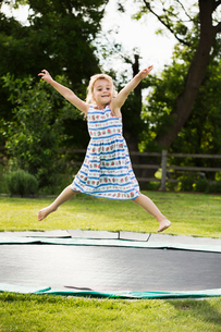 Girl in a sundress jumping on a trampoline set in the ground, in a garden.の写真素材 [FYI02258084]