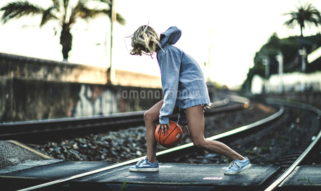 Young woman running across railway tracks bouncing a basketball.の写真素材 [FYI02258086]