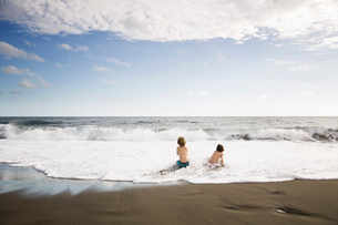 Two children, young boys playing at the water's edge on a sandy beach.の写真素材 [FYI02258095]