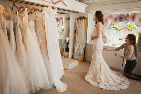 Rows of wedding dresses on display. A young woman in a full length white wedding dress, looking at hの写真素材 [FYI02258098]