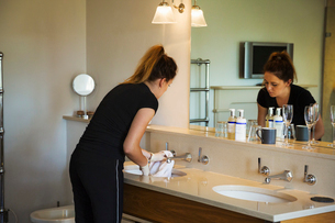 Woman standing in a hotel bathroom in front of mirror, cleaning sink.の写真素材 [FYI02258101]